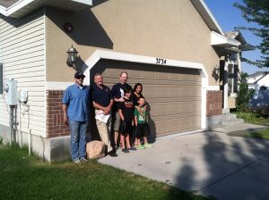 Vince Newburg and family stand in front of their home that has just had sprinklers installed via the Home Safe Initiative.